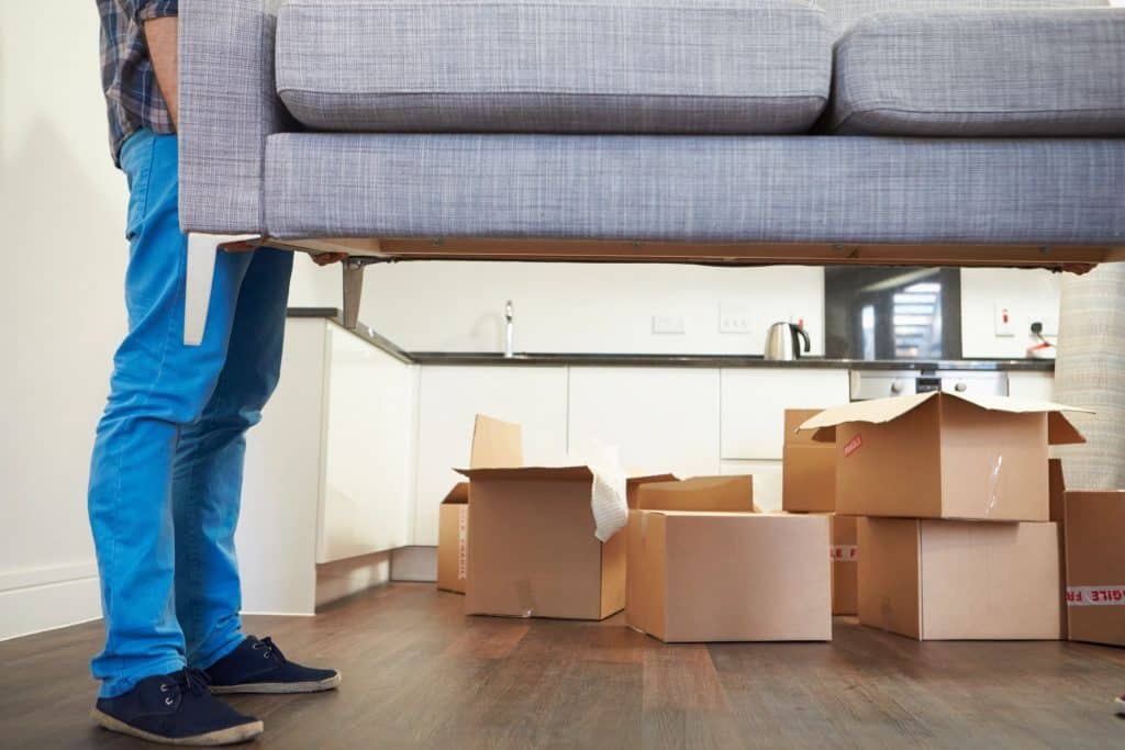moving company employee lifting couch in house with boxes in background