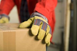 worker with heavy-duty gloves moving boxes