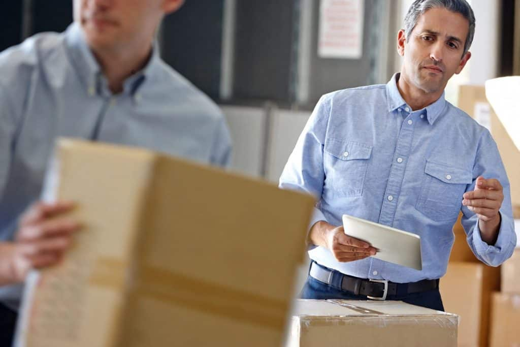 man watching moving company employees pack up a house