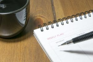 pencil writing in a paper calendar next to a cup of coffee