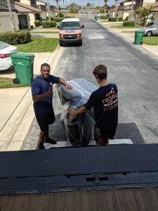 Two Tropic Moving employees putting furniture into the truck