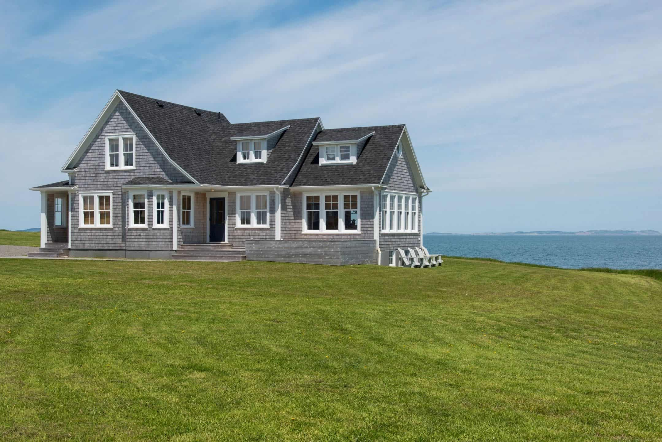 grey two-story house on a grassy lawn by the ocean