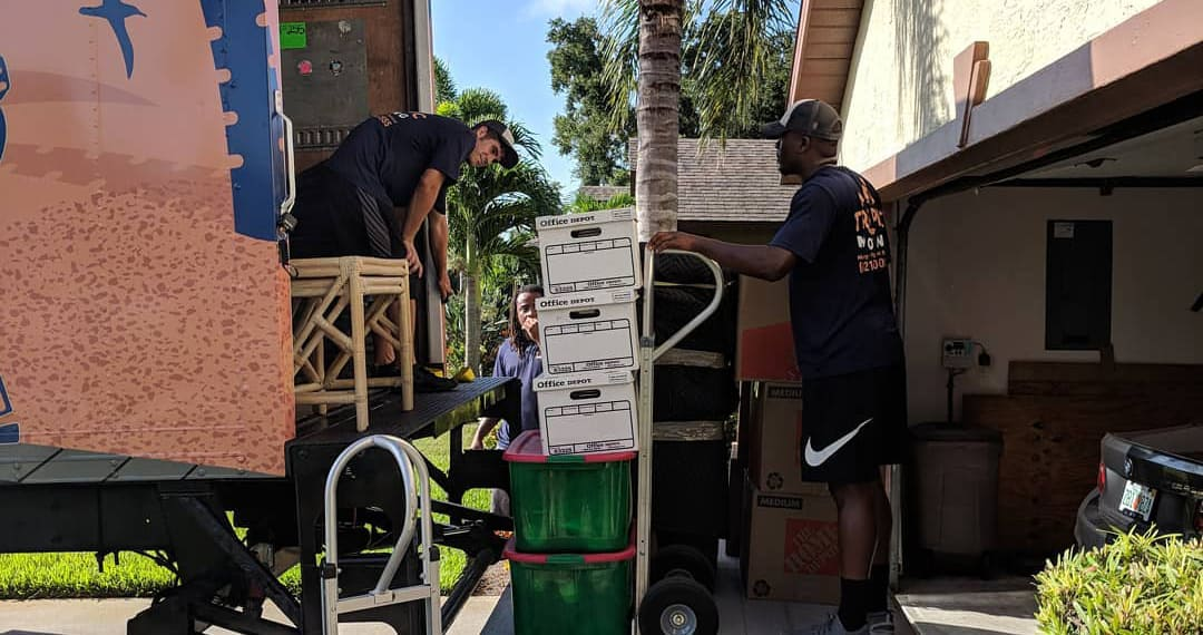 Tropic Moving employees putting boxes into the moving truck