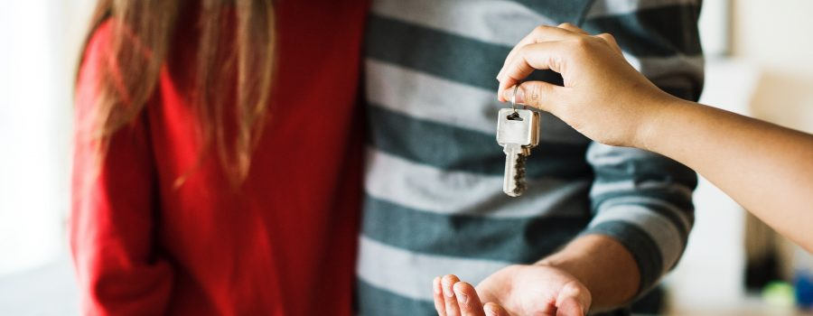 a young couple being handed the keys to an apartment