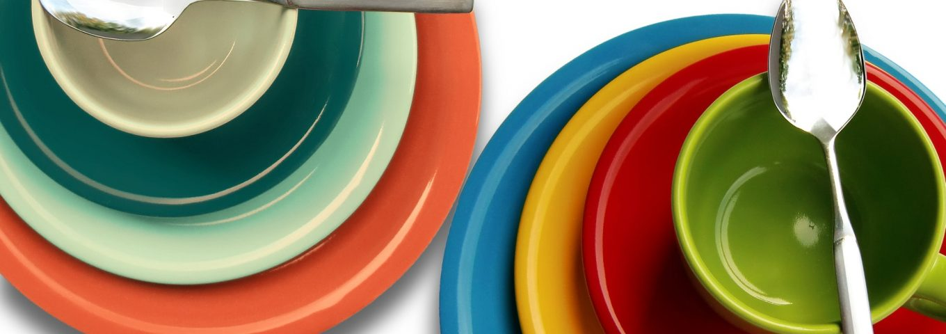 colorful sets of plates, bowls, and cups stacked with a spoon on top