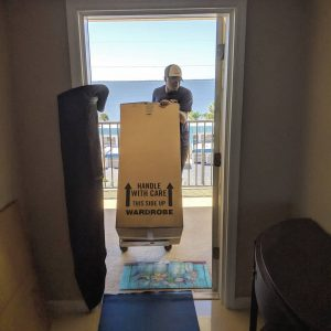 Tropic Moving employee moving a wardrobe from a condo