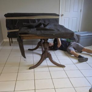 Tropic Moving company employee wrapping a table for a move