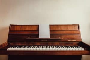 antique brown Hupfeld piano against a white wall