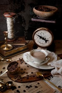 coffee in an antique teacup with coffee beans and vintage items