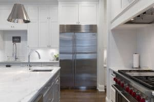 clean, white kitchen with stove, refrigerator, and countertop