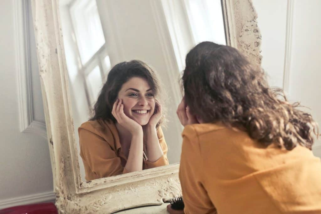 girl looking into mirror in home