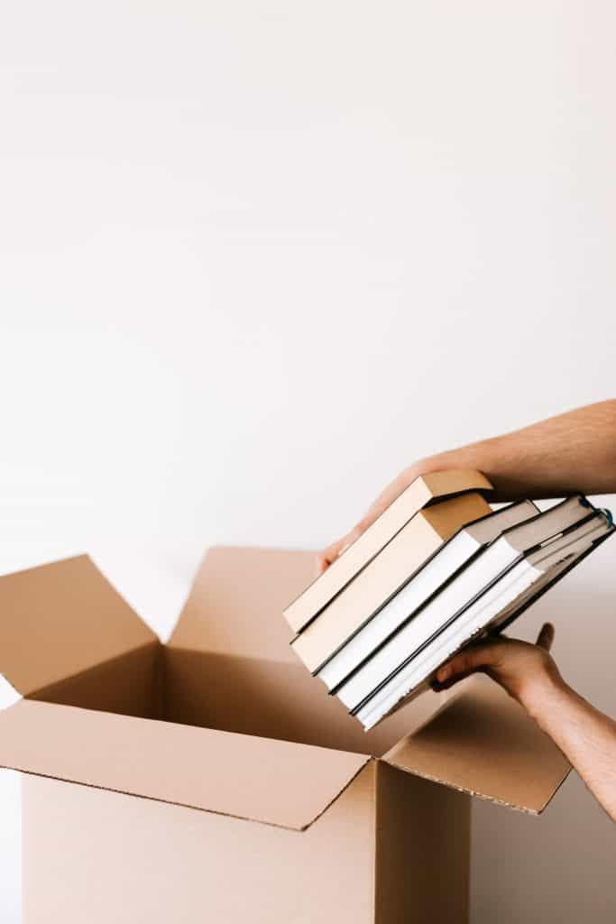 person putting books in moving box