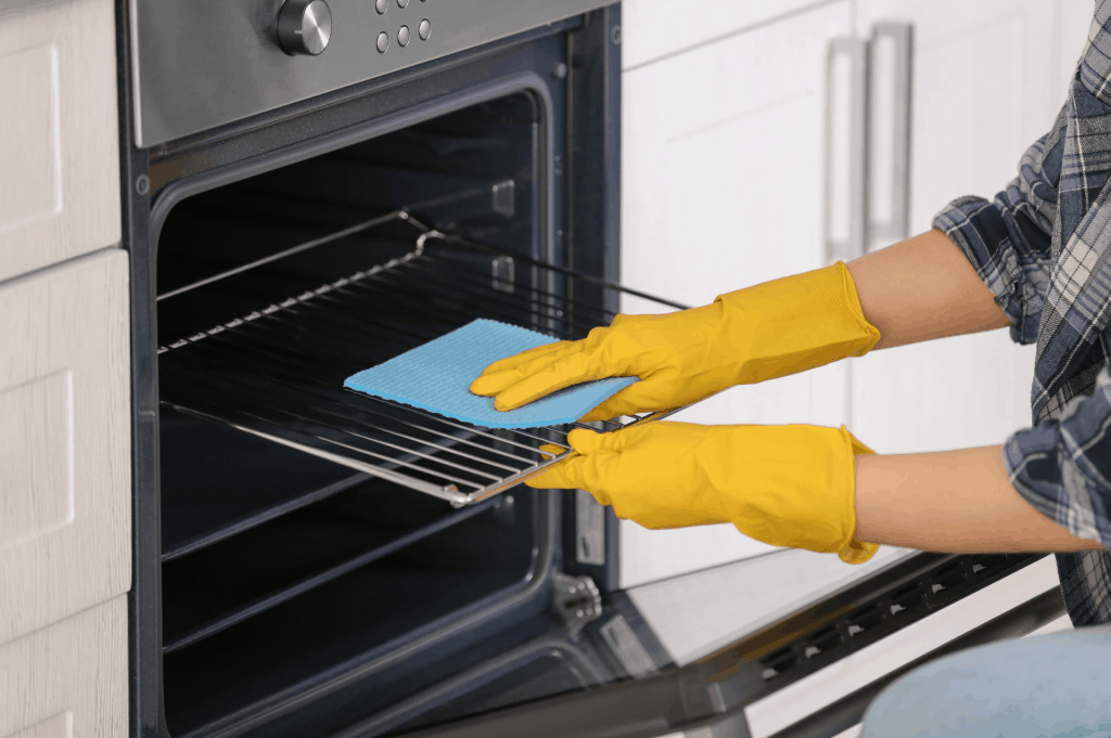 woman cleaning the oven rack in kitchen