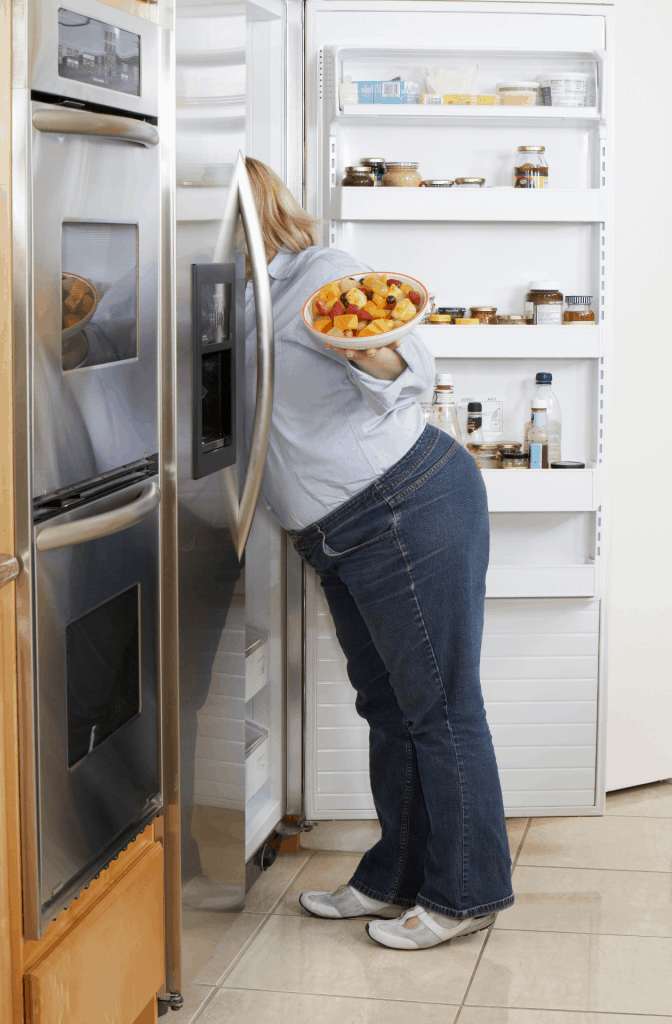woman getting fruit out of fridge